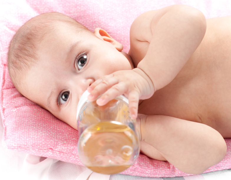 3 months adorable  baby girl drinking from plastic bottle in her